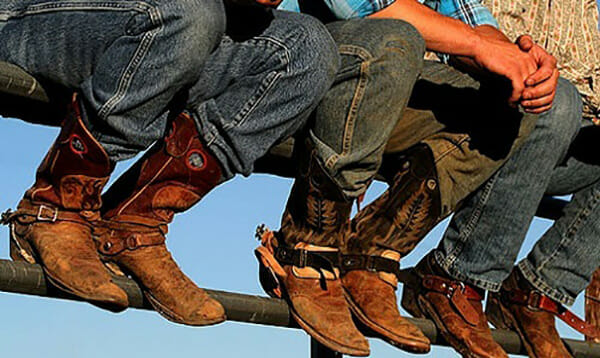 Cowboy Boots And Jeans - Cowboys sitting on fence wearing jeans and boots